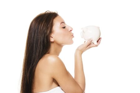 beautiful brunette woman kissing a piggy bank on white background photo