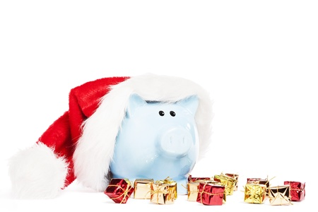 piggy bank wearing santas hat with tiny christmas presents on white background photo