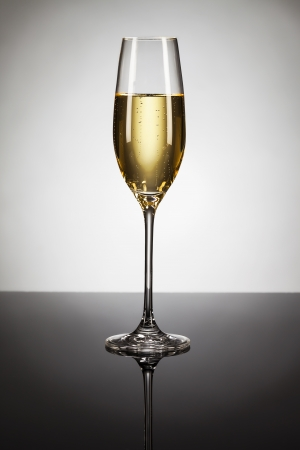 glass of champagne on a mirror with spot in background Stock Photo