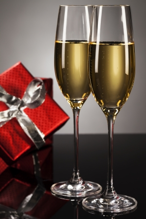 two glasses of champagne with a red present in background on a mirror photo