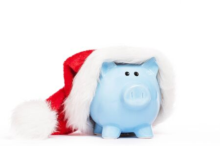 blue piggy bank wearing santas hat on white background photo