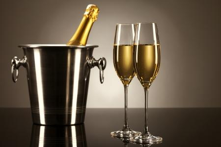 botella champagne: dos copas de champán con una botella de champán en un cubo sobre un espejo con luz de spot