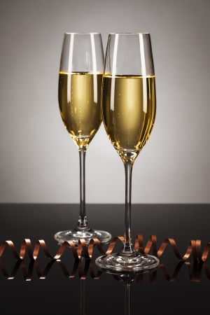 two glasses of champagne with a streamer on a mirror with a spot light background photo