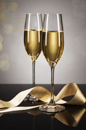 two glasses of champagne with a golden ribbon on a mirror with a spot light background