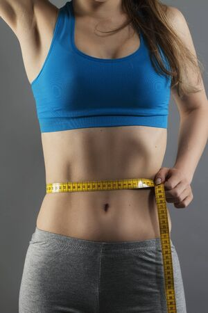 closeup of a woman measuring her waist on gray background photo