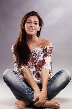 long legged: happy brunette woman wearing blue jeans sitting on the floor