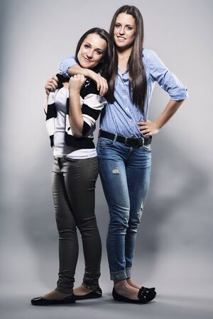 teenager hugging her sister on gray background Stock Photo - 17413673