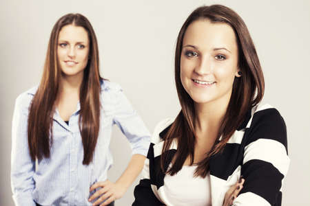 happy teenager in front of other brunette teenager Stock Photo - 17413668