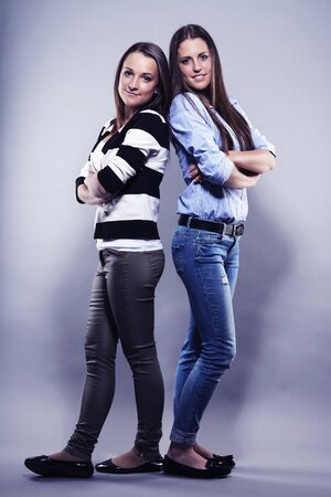 two teenager standing back to back on gray background Stock Photo - 17413633