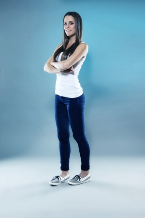 pretty sporty teenager with crossed arms in blue light photo