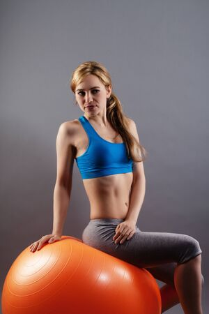 beautiful fitness woman sitting on a exercise ball on gray background photo