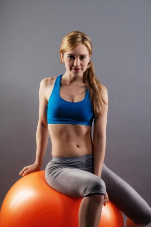 girl fitness: confident fitness woman sitting on a orange exercise ball on gray background Stock Photo