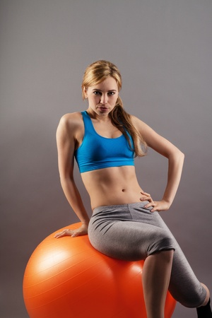 beautiful blonde fitness woman sitting on a orange exercise ball on gray background photo