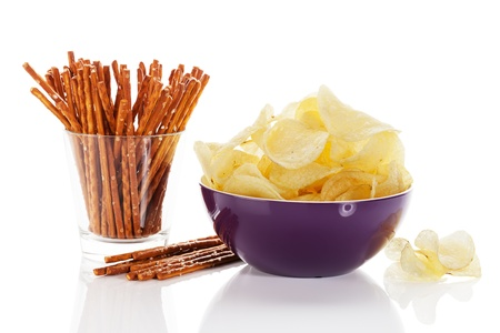 pretzel: potato chips in a bowl with pretzel sticks in a glass on white background