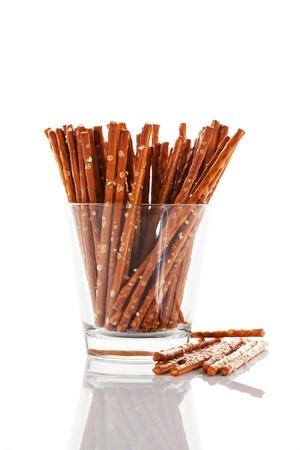 pretzels: pretzel sticks in a glass on white background