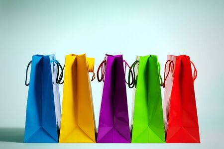 five colorful shopping bags in a row in fashion light photo