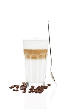 latte macchiato with a standing spoon and coffee beans on white background