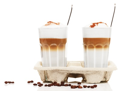 two latte macchiato with chocolate powder in a cupholder with coffee beans  and spoons on white background photo