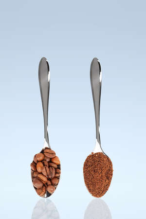 grinded: coffee beans and grinded coffee on standing spoons with blue background Stock Photo