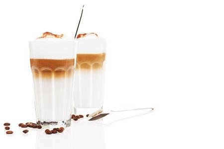 latte macchiato: two glasses latte macchiato with coffee beans and chocolate powder on white background Stock Photo