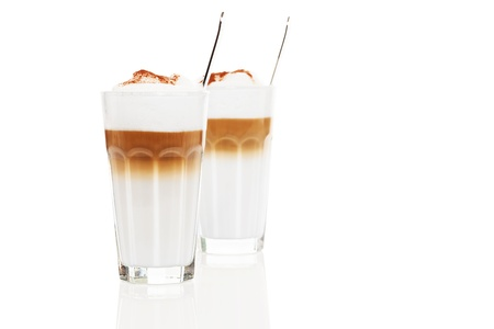 two glasses latte macchiato with chocolate powder and spoons inside on white background