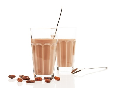 chocolate milk in front of other chocolate milk with chocolate beans and spoons on white background photo