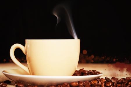 granos de cafe: humeante taza de caf� con granos de caf� en una tela de yute con fondo negro