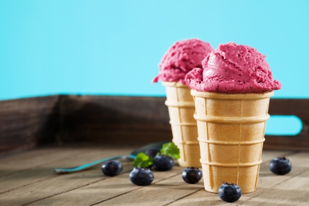 speiseeis: Blaubeer-Eis in Waffeln auf Holz mit blauem Hintergrund Lizenzfreie Bilder