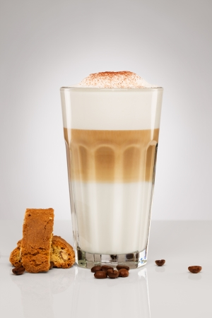 amaretto: latte macchiato with chocolate powder coffee beans and cantuccini cookies on gray background Stock Photo