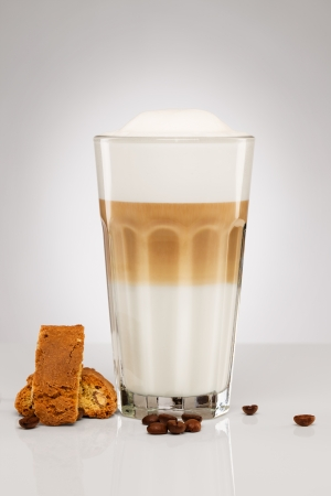 amaretto: latte macchiato with coffee beans and cantuccini cookies on gray background