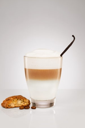 small latte macchiato with a vanilla bean coffee beans  and a cantuccini cookie on gray background photo