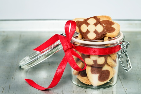 a jar filled with christmas cookies on a silver metal tray photo