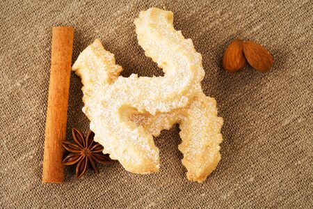 butter cookies with anise, cinnamon sticks and almonds from top on a fabric photo