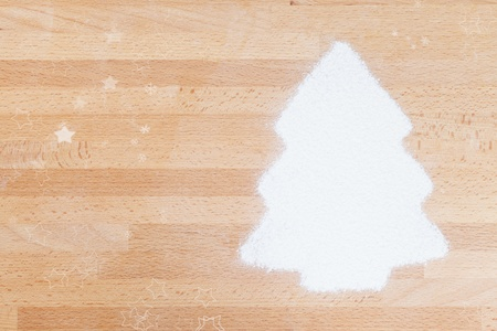 flour in shape of a christmas tree with copy space and stars on wooden background photo