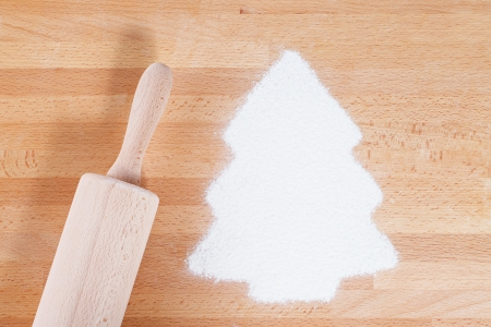 flour in shape of a christmas tree with a rolling pin from top on wooden background photo