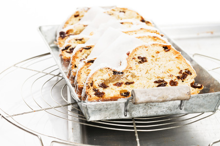 traditional christmas stollen cake on a rustic metal tray on a cooling grid photo