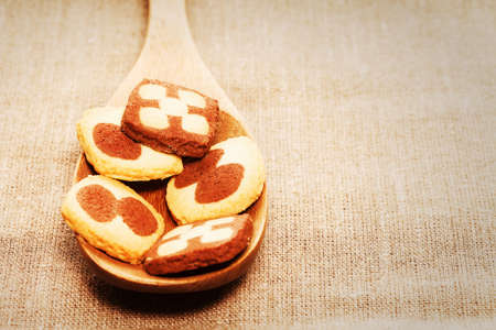closeup of christmas cookies on a wooden spoon on linen fabric photo
