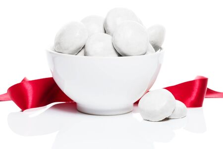 white gingerbread lebkuchen cookies with sugar icing in a white bowl with a red ribbon on white background photo