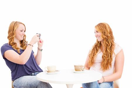 femme rousse faire des photos de son ami heureux sur fond blanc
