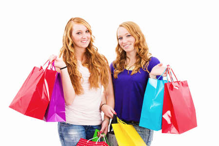 two happy redhead women with shopping bags on white background photo