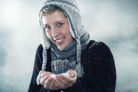 young happy woman wearing winter clothes showing a hand full of snow photo