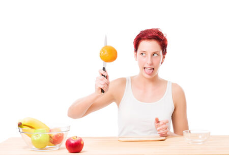 funny woman trying to cut a orange on white background photo