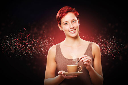 happy redhead woman with a coffee cup on black with particles photo