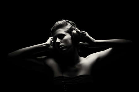 gorgeous woman in black and white tense light listening to music photo