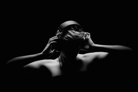 blonde woman listening to music in black and white tense light photo