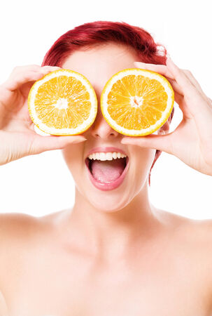 excited happy young redhead woman holding oranges over her eyes on white background photo