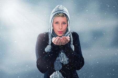 young woman in winter blowing snow off her hands photo