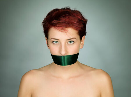 woman with her mouth bond with a green ribbon photo