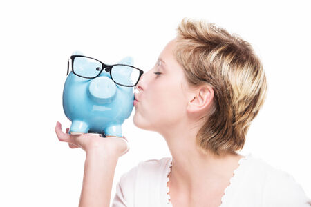 young blonde woman kissing a blue piggy bank on white background photo