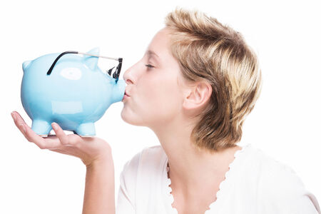 blonde woman kissing a piggy bank which is wearing glasses on white background photo